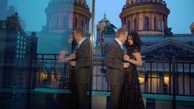 Giovane uomo caucasican in vestito e donna castana sexy in vestito di lusso nero che resta al balcone in una città video d archivio