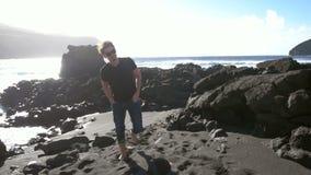 Giovane uomo caucasico che cammina a partire dall'oceano stock footage