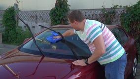 Giovane uomo caucasico che lava la sua automobile sul self service dell'autolavaggio Automobile washing stock footage