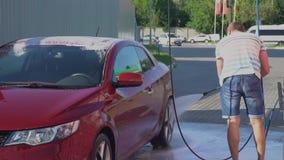 Giovane uomo caucasico che lava la sua automobile sul self service dell'autolavaggio Automobile washing video d archivio