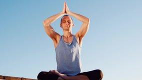 Giovane uomo caucasico che si rilassa praticando esercizio di forma fisica di yoga sulla spiaggia vicino al fiume calmo con la ci archivi video