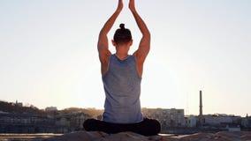 Giovane uomo caucasico che si rilassa praticando esercizio di forma fisica di yoga sulla spiaggia vicino al fiume calmo con la ci stock footage