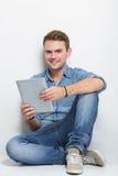 Giovane uomo caucasico che si siede sul pavimento che tiene un pc della compressa Fotografia Stock