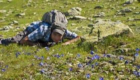 Giovane uomo caucasico che si trova sull'erba con i fiori Immagini Stock