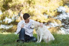 Giovane uomo caucasico con il cane molto vecchio nel parco Fotografia Stock Libera da Diritti