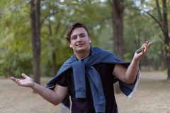 Giovane uomo caucasico con le mani di scrollate di spalle dei capelli scuri in perdita, tenendo un cacciavite Difficoltà tecniche fotografia stock libera da diritti