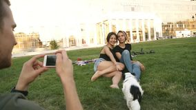 Giovane uomo caucasico con uno smartphone che prende immagine dei suoi due bei amici femminili le ragazze stanno sedendo sul verd video d archivio