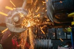 Giovane uomo caucasico in indumenti da lavoro rossi che riparano automobile con la taglierina di angolo immagine stock