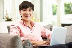 Giovane uomo cinese che per mezzo del computer portatile mentre distendendosi Fotografia Stock Libera da Diritti