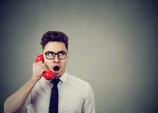 Giovane uomo colpito di affari che parla su un telefono rosso Immagini Stock Libere da Diritti