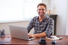 Giovane uomo d'affari adulto che sorride alla macchina fotografica mentre sedendosi allo scrittorio Immagine Stock
