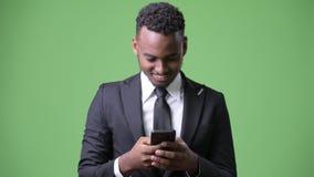 Giovane uomo d'affari africano bello contro fondo verde stock footage