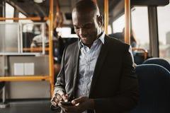 Giovane uomo d'affari africano che ascolta la musica nel corso della sua mattinata fotografia stock libera da diritti