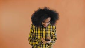 Giovane uomo d'affari africano felice che per mezzo del telefono ed ottenendo buone notizie su fondo arancio Concetto delle emozi video d archivio