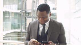 Giovane uomo d'affari afroamericano che passa in rassegna con lo smartphone, stante nel centro di affari video d archivio