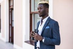 Giovane uomo d'affari afroamericano risoluto facendo uso del binocolo in ufficio fotografie stock