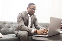 Giovane uomo d'affari afroamericano in un vestito grigio che lavora dietro un computer portatile fotografia stock libera da diritti