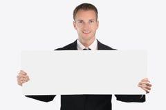 Giovane uomo d'affari allegro che mostra insegna in bianco Fotografie Stock Libere da Diritti
