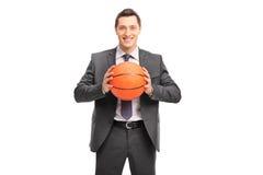 Giovane uomo d'affari allegro che tiene una pallacanestro fotografia stock