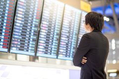 Giovane uomo d'affari asiatico che controlla il suo volo Fotografia Stock