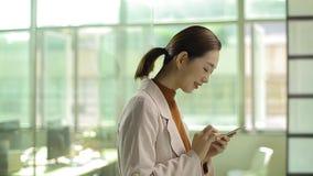 Giovane uomo d'affari asiatico che fa una chiamata in ufficio stock footage