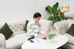 Giovane uomo d'affari asiatico che lavora al suo computer portatile in una caffetteria Fotografia Stock Libera da Diritti