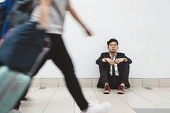 Giovane uomo d'affari asiatico sciatto che si siede al passaggio pedonale che pensa al suo problema immagini stock libere da diritti