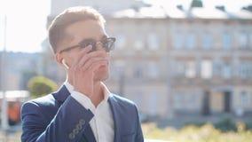 Giovane uomo d'affari attraente che parla sul telefono facendo uso delle cuffie senza fili che camminano fuori Colloqui felici de archivi video