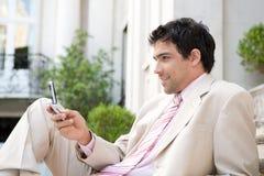 Uomo d'affari facendo uso del telefono cellulare. Immagine Stock Libera da Diritti