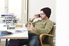 Giovane uomo d'affari attraente dei pantaloni a vita bassa che lavora dal Ministero degli Interni con il telefono cellulare immagini stock