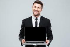 Giovane uomo d'affari attraente felice che tiene il computer portatile dello schermo in bianco Fotografie Stock