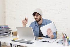 Giovane uomo d'affari attraente ispanico dei pantaloni a vita bassa che lavora al Ministero degli Interni moderno Fotografia Stock