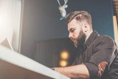 Giovane uomo d'affari barbuto in camicia marrone che si siede alla tavola e che lavora al computer portatile Free lance che lavor Immagine Stock
