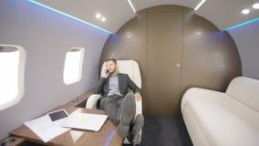 Giovane uomo d'affari barbuto che discute affare durante il volo, sedentesi in aereo privato stock footage
