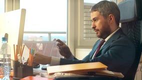 Giovane uomo d'affari barbuto che effettua pagamento online con la sua carta di credito Fotografia Stock Libera da Diritti