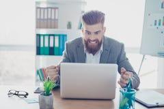 Giovane uomo d'affari barbuto frustrato che urla al suo computer portatile dentro di immagini stock libere da diritti