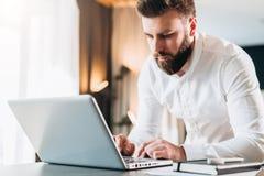 Giovane uomo d'affari barbuto serio che sta nell'ufficio vicino alla tavola e che per mezzo del computer portatile L'uomo lavora  fotografia stock libera da diritti