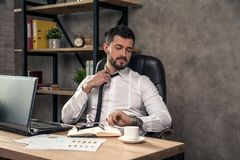 Giovane uomo d'affari bello alla moda che lavora al suo scrittorio nell'ufficio che ripara il suo legame e che esamina l'orologio fotografie stock libere da diritti