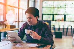 Giovane uomo d'affari bello asiatico concentrato mentre leggendo il suo Immagine Stock Libera da Diritti