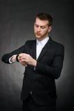 Giovane uomo d'affari bello che esamina orologio Fotografia Stock