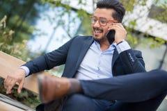 Giovane uomo d'affari bello che parla sul suo smartphone mentre sittin immagine stock