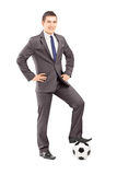 Giovane uomo d'affari bello che posa con un calcio Immagine Stock Libera da Diritti