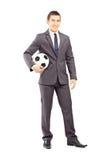 Giovane uomo d'affari bello che tiene un calcio Immagini Stock
