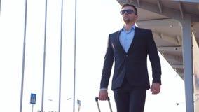 Giovane uomo d'affari bello che va con i bagagli dall'aeroporto sulla via della città Uomo sicuro in un vestito nero che cammina  stock footage