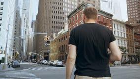 Giovane uomo d'affari bello con i documenti che stanno strada vicina, andante lavorare in ufficio a New York, America Movimento l stock footage