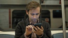 Giovane uomo d'affari bello con lo smartphone in sottopassaggio, studente dell'uomo nel pubblico di trasportation della stazione  video d archivio