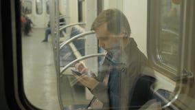 Giovane uomo d'affari bello con lo smartphone in sottopassaggio, studente dell'uomo nel pubblico di trasportation della stazione  stock footage
