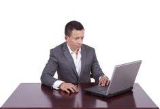 Giovane uomo d'affari bello facendo uso del computer portatile Fotografia Stock Libera da Diritti
