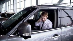 Giovane uomo d'affari bello facendo uso dello smartphone, sedentesi in nuova automobile nel centro dell'automobile video d archivio
