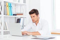 Giovane uomo d'affari bello premuroso che si siede alla tavola con il computer portatile immagine stock libera da diritti